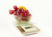 Scales with grapes, lime and orange Stock Photos