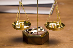 Scales of Justice!. Scales of justice closeup on desk with dark background Royalty Free Stock Image