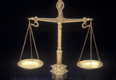 Scales of Justice. Gold scales with black background Royalty Free Stock Photo