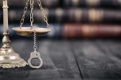 Scales of Justice and handcuffs on a black wooden background. Law and Justice, Legality concept, Scales of Justice and handcuffs on a black wooden background stock image
