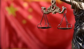 Scales of Justice, Justitia, Lady Justice in front of the flag of China. Stock Image