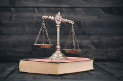 Scales of Justice and law books on a wooden background. Royalty Free Stock Images