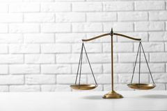 Scales of justice on table against brick wall. Law concept stock photos