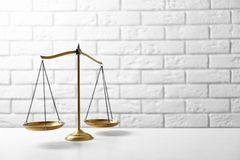Scales of justice on table against brick wall. Law concept royalty free stock images