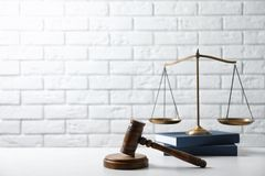 Scales of justice, wooden gavel and books. On table against brick wall. Law concept stock image