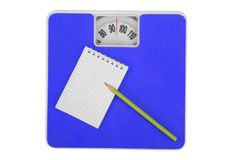 Scales and notebook with a pencil. Royalty Free Stock Photo