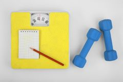 Scales, notebook with pencil and a dumbbell. Stock Photos