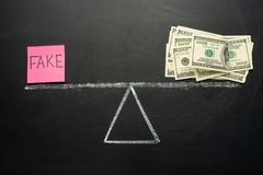 Scales with truth and fake. The concept on the blackboard. Place of truth is us dollars. The concept of corruption, and not the ve stock photo