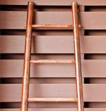Scaletta di bambù che pone sulla parete di legno immagini stock