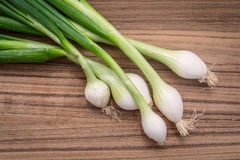 Scallions on a wooden board Royalty Free Stock Photo