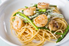 Scallop asparagus cream pasta. Delicious seared scallop and garlic asparagus in white cream pasta Royalty Free Stock Photo