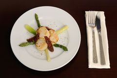 Scallop with an asparagus. On a white dish royalty free stock image