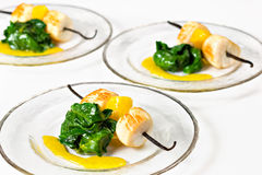 Scallop Recipe. Scallop on vanilla skewers with spinach and mango sauce Stock Image