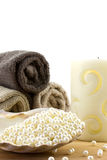 Scallop shell filled with pearl beads. And towels  and candle on the background isolated Stock Image