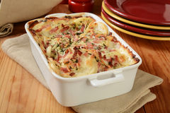 Scalloped potato casserole. Scalloped potatoes in cheese sauce with ham in a casserole dish Stock Photography