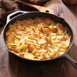 Scalloped potatoes in rustic iron skillet. Close up photo of scalloped potatoes in rustic iron skillet Stock Images
