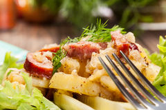 Scalloped potatoes with sausage and bacon. On a plate Royalty Free Stock Photo