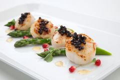 Scallops and Black Caviar. Close up of delicious appetizer scallops with black caviar. Garnished with asparagus, pomegranate seeds, microgreens, and sauce. Elite Stock Photo