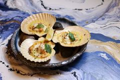 Scallops on blue plate with lemon. On a blue background Royalty Free Stock Photos