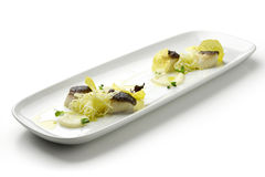 Scallops in a crust of black rice with cream of celery rapa Royalty Free Stock Photography