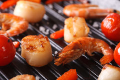 Scallops, shrimp and vegetables on grill macro. Horizontal Royalty Free Stock Photography