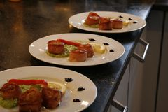 Scalops. Three prepared plates with scallops in raw ham with a mash of green peas Stock Image
