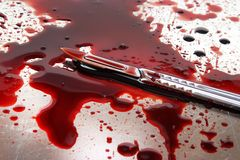 Scalpel with blood. Surgeon knife on stainelss steel autopsy table with lot of blood Stock Photos