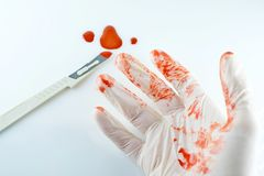 The scalpel in blood and hands of the doctor. Isolated Royalty Free Stock Image