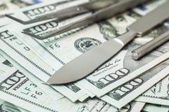 Scalpel et brucelles sur la pile des dollars de factures d'argent liquide Chirurgie chère de concept, assurance-maladie photographie stock