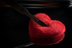 Scalpel on red heart,medical background. Stock Photos