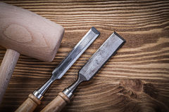 Scalpelli piani del martello del grumo sulla costruzione del legno d'annata del bordo concentrata Immagini Stock
