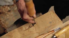 Scalpello nelle mani di un carpentiere professionista il carpentiere tratta gli strumenti di legno di carpenteria della plancia 4 video d archivio