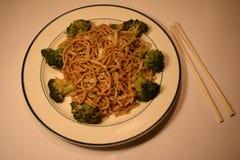Scalpore cinesi Fried Lo Mein Noodles In un piatto bianco con i bastoncini su un fondo bianco immagine stock