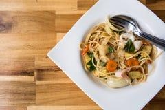 Scalpore Fried Sea Bass degli spaghetti sulla tavola di legno immagini stock