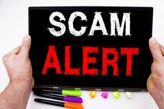 Scam alerta o texto escrito na tabuleta, computador no escritório com marcador, pena, artigos de papelaria Conceito do negócio pa fotos de stock royalty free