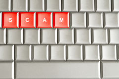 Scam word spelled on a metallic keyboard Stock Photo