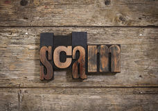 Scam written with letterpress type Royalty Free Stock Photos