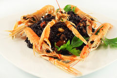 Scampi and black rice. Langoustines scampi and black rice Stock Photos