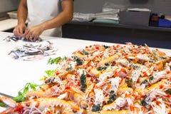 Scampi freschi e mani che preparano pesce al mercato Fotografia Stock
