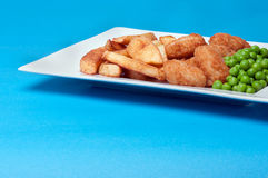Scampi, fries and peas. On a white rectangular white plate Stock Images