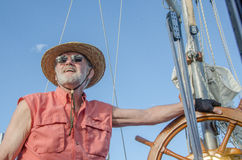 Scan the Horizon. A retired man at the helm of his classic ketch enjoys the summer day under a bright blue sky stock image