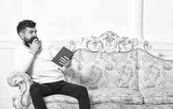 Scandalous bestseller concept. Guy reading book with amazement. Man with beard and mustache sits on baroque style sofa. Holds book, white wall background stock photography