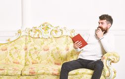 Scandalous bestseller concept. Guy reading book with amazement. Man with beard and mustache sits on baroque style sofa. Holds book, white wall background stock images