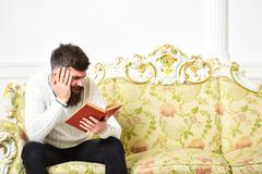 Scandalous bestseller concept. Guy reading book with attention. Man with beard and mustache sits on baroque style sofa. Holds book, white wall background royalty free stock photos