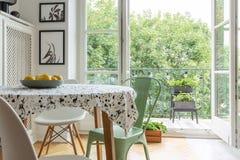 Scandi matsalinre med en mönstrad torkduk på en tabell, stolar och balkong i bakgrunden royaltyfria foton
