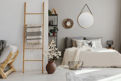 Scandi open space bedroom interior with bed with knit blanket and many pillows, rack with books and decor, carpet on the stock photos