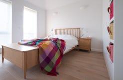 Scandi projektuje sypialni wnętrze z drewnianym sypialnia meble, biel malować ścianami, białą pościelą i colourful koc, zdjęcia stock