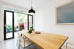 Scandi styled dining room interior with outlook to courtyard via. Scandi styled dining room interior with outlook to courtyard through open french doors Stock Image
