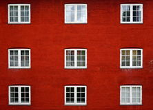 Scandinavian architecture. Red wall and nine white windows. Beautiful symetry Royalty Free Stock Images