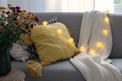Scandinavian autumn inspired home decor - cozy Living room, Sofa Cushion, knitted plaid, garland, traw basket, mums flowers royalty free stock photography